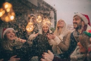 Photo of a group of friends celebrating New Year's and Christmas holidays by throwing a party on the balcony over the city, while it is snowing