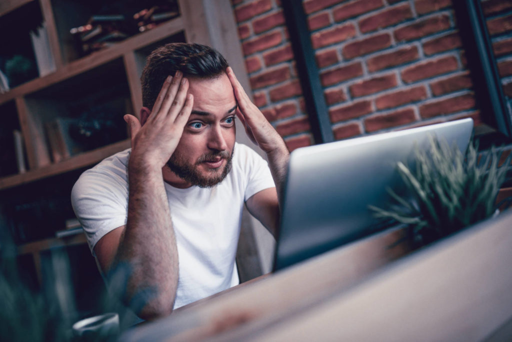 Man working at coffee shop looks shocked and distressed at his laptop