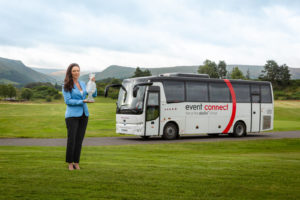 Woman poses on a field beside an Event Connect bus